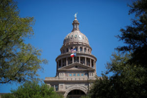 The U.S flag and the Texas State flag fly over the Texas State Capitol as the state senate debates the #SB6 bathroom bill ...