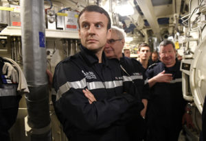 """French President Macron looks on as he stands with crew of the submarine """"Le Terrible"""" and Chief of the Special General St..."""