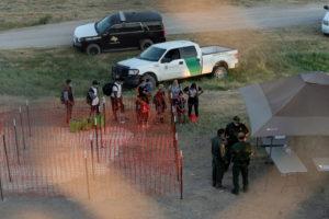 Asylum-seeking migrants wait to be processed under the International Bridge in Del Rio