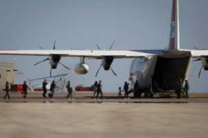 Migrants board a U.S. Coast Guard airplane at the Del Rio International Airport as U.S. authorities accelerate removal of ...