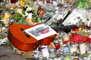 """A guitar with a message bearing France's national motto """"Liberte, Egalite, Fraternite"""", is seen among flowers left in trib..."""
