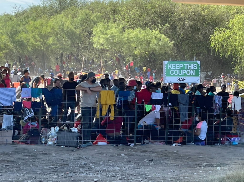 Migrants stand by the International Bridge between Mexico and the U.S., in Del Rio