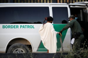 A U.S. Border Patrol officer assists a migrant seeking asylum in the U.S. near the International Bridge between Mexico and...
