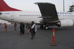 Taliban members stand on airport runway in Kabul