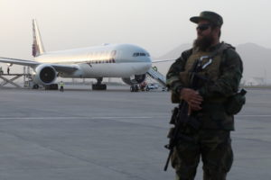 A member of Taliban security forces stands guard in front of a Qatar Airways airplane boarding passengers, in Kabul