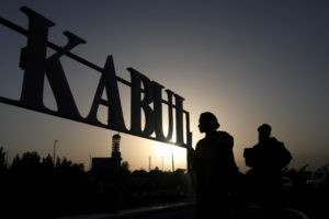 Taliban soldiers stand in front of a sign at the international airport in Kabul