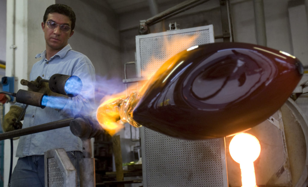 Master glassmaker Simone Cenedese uses a blowtorch on a piece of commissioned work at his family's furnace on the island o...