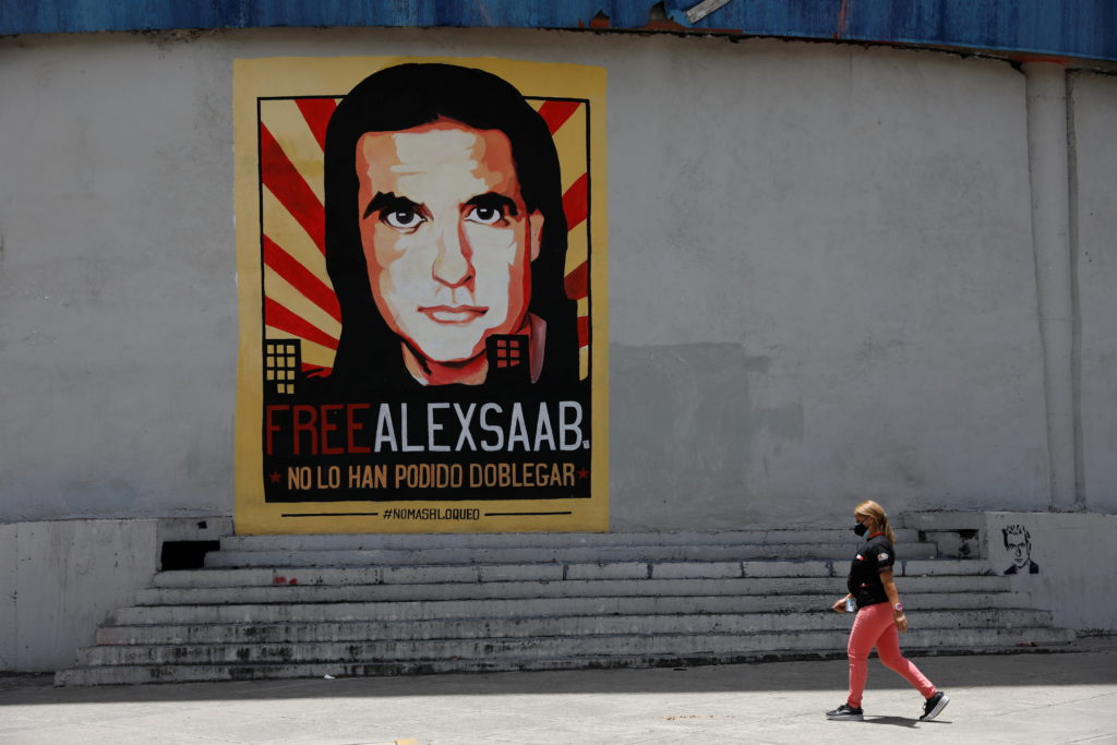 A woman walks by a mural in support of the liberation of Colombian businessman and envoy Alex Saab, who is detained in Cap...