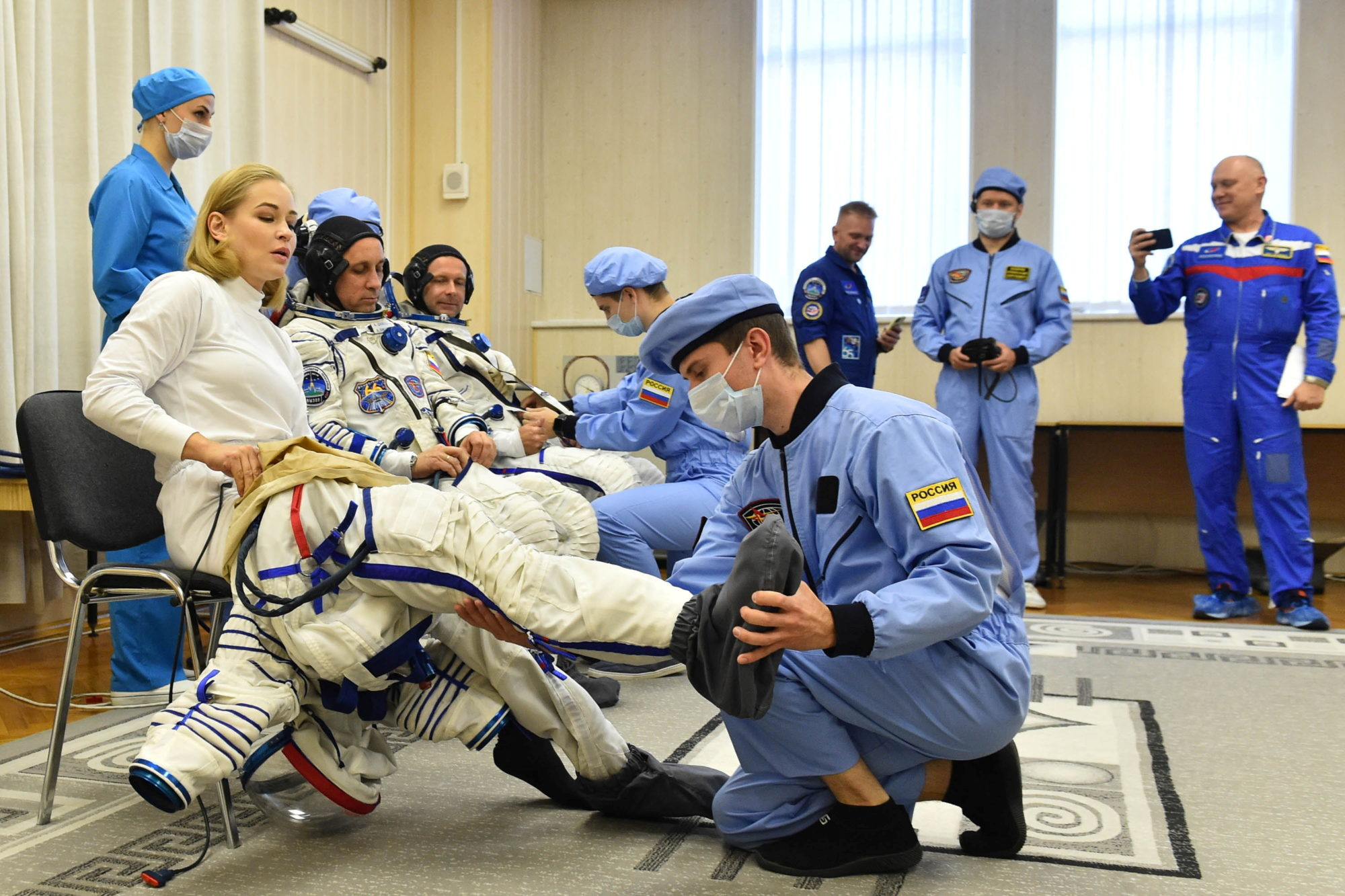 The International Space Station (ISS) crew members donning space suits shortly before the launch at the Baikonur Cosmodrome