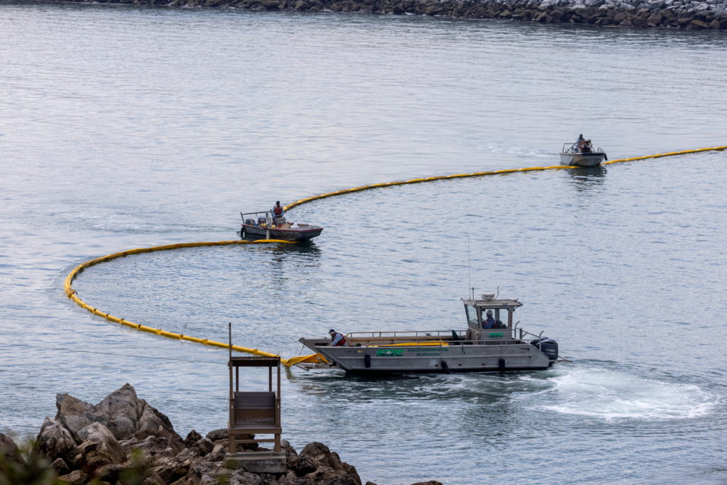 FILE PHOTO: Workers seal off Newport Beach harbor as a major California oil spill moves south down the coast