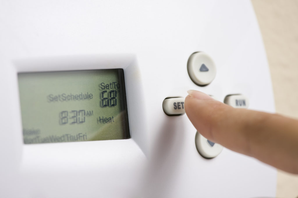 A person sets an electronic thermostat heat to 68 degrees.