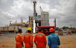 Technicians stand next to an oil rig which is manufactured by Megha Engineering and Infrastructures Limited (MEIL) at an O...