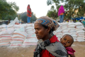 FILE PHOTO: Woman carries an infant as she queues in line for food, at the Tsehaye primary school, in Shire