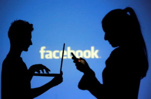 FILE PHOTO: FILE PHOTO: People pose with laptops in front of projection of Facebook logo in this picture illustration take...